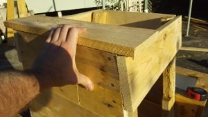 When attaching your new top piece to the frame, hold a piece of timber on top as shown. This makes sure that your new slat won't get in the way of the lid later.