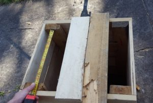 Measure the distance between the top of your legs, and cut two pieces of scrap to fit. You can do this in either direction, your finished, visible lid slats will lay perpendicular (90 degrees) to this measurement.